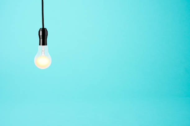 Hanging a illuminated light bulb on blue background stock photo