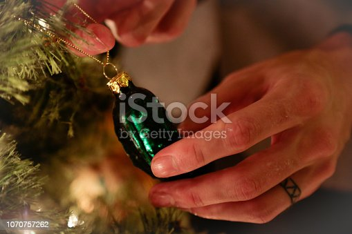 A man hanging up a unique pickle ornament on a Christmas tree