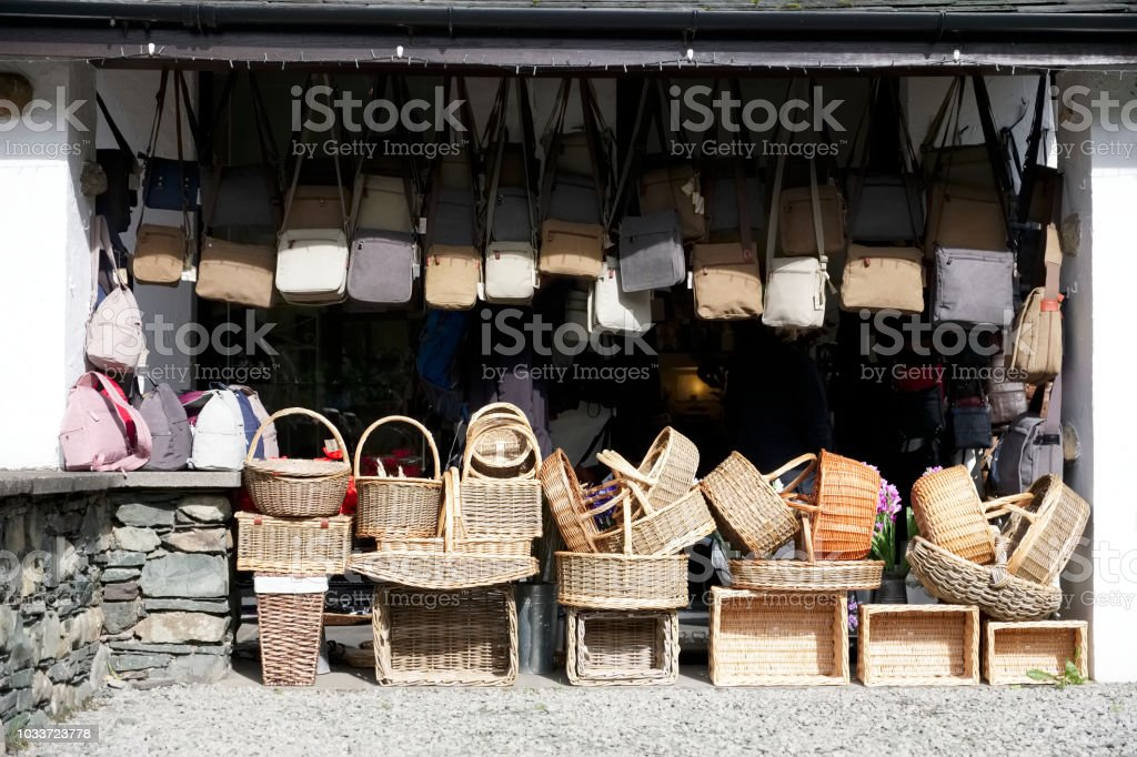 Hanging bags and baskets at market store shop outdoors in sun stock photo