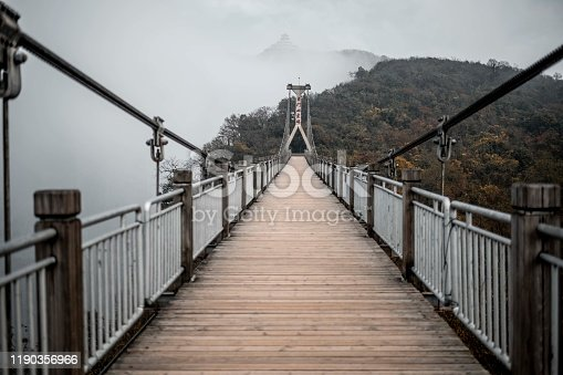 A suspension bridge with Chinese writing on the center pillar on the Tianmen mountain (天门山), Zhangjiajie (张家界).  NOTE TO INSPECTION: Image adjusted