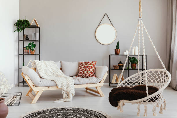 hanging chair near grey wooden sofa in ethno living room interior with round mirror. real photo - home decor boho imagens e fotografias de stock