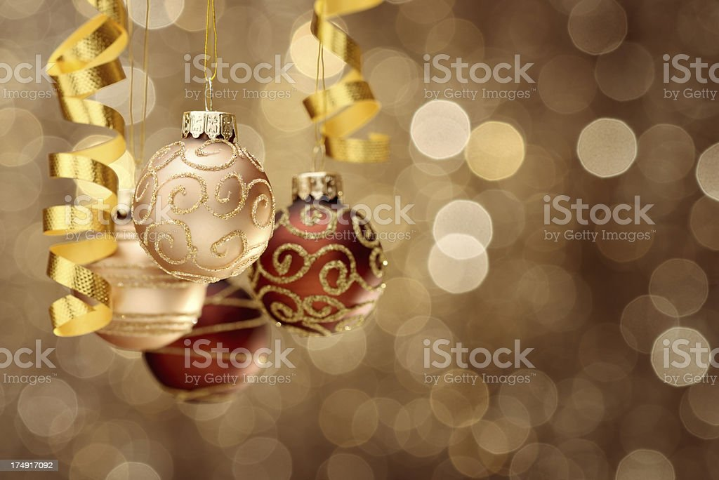 Hanging christmas balls on gold-brown illuminated background royalty-free stock photo