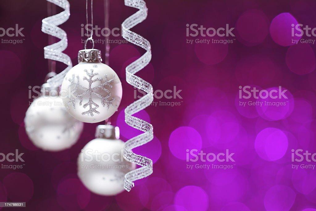 Hanging christmas balls on purple illuminated background royalty-free stock photo