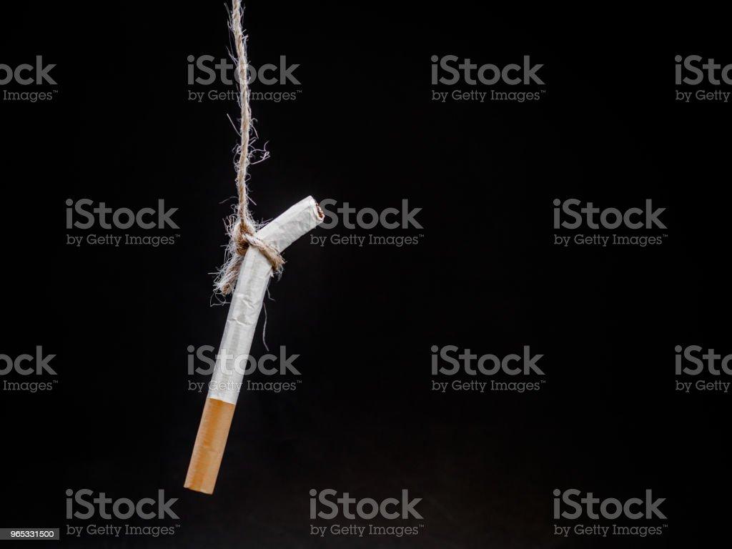 pendaison de cigarete sur fond noir. vous tuer.  Concept de fumer arrêter de fumer. monde la journée sans tabac - Photo de Adulte libre de droits