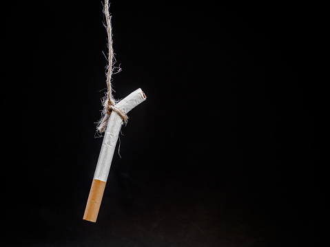 Photo libre de droit de Pendaison De Cigarete Sur Fond Noir Vous Tuer Concept De Fumer Arrêter De Fumer Monde La Journée Sans Tabac banque d'images et plus d'images libres de droit de {top keyword}