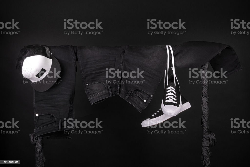 Hanging clothing. Black and white sneakers, cap  jeans on clothes foto stock royalty-free
