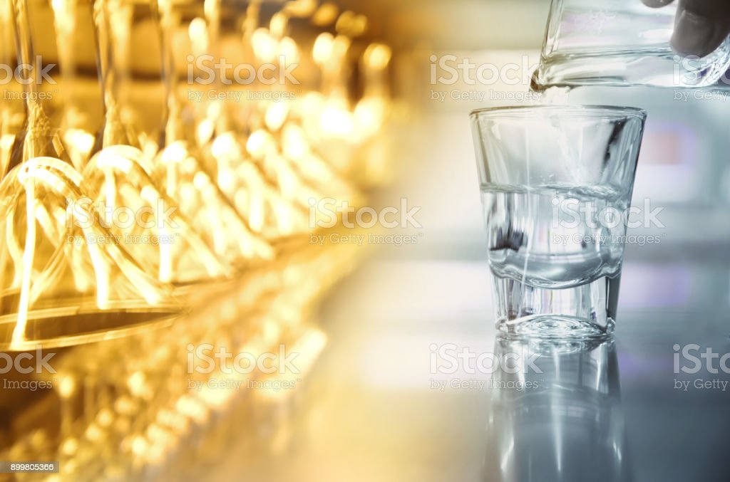 hanging cocktail party glass with alcohol shot glass with drink liquor in club or bar background stock photo