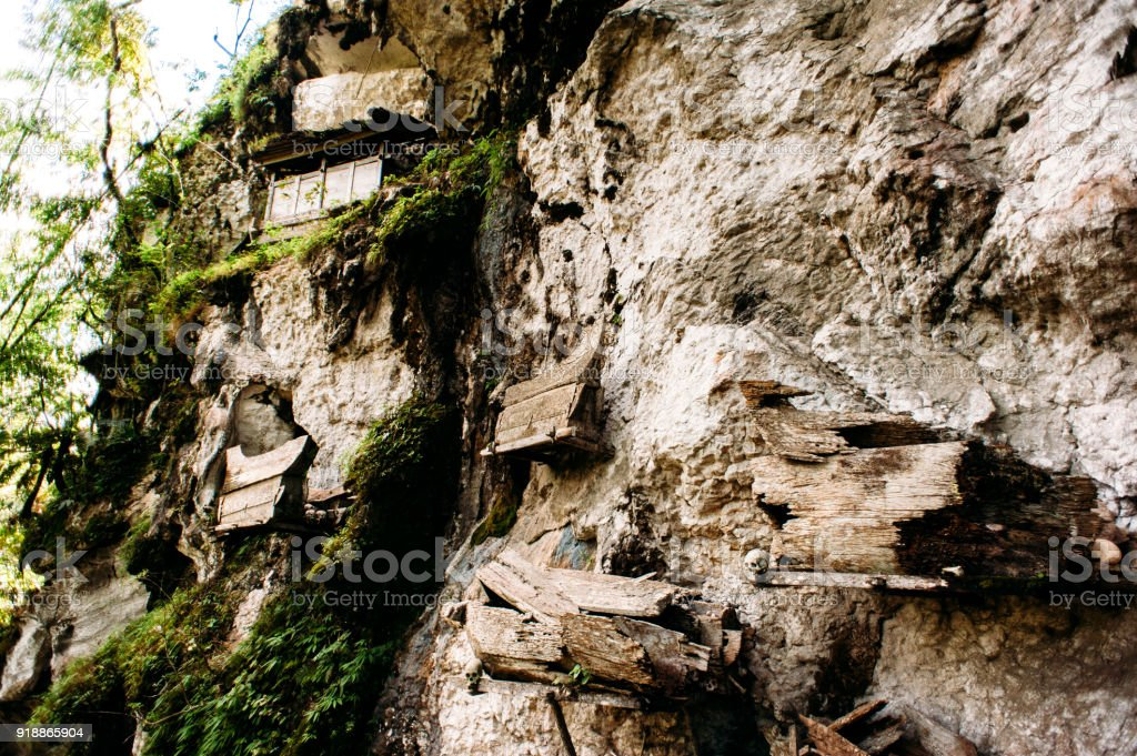 Hanging coffins, graves. Old coffin with skulls and bones nearby on a rock. Traditional burials site, cementery Kete Kesu in Rantepao, Tana Toraja, Sulawesi, Indonesia. stock photo