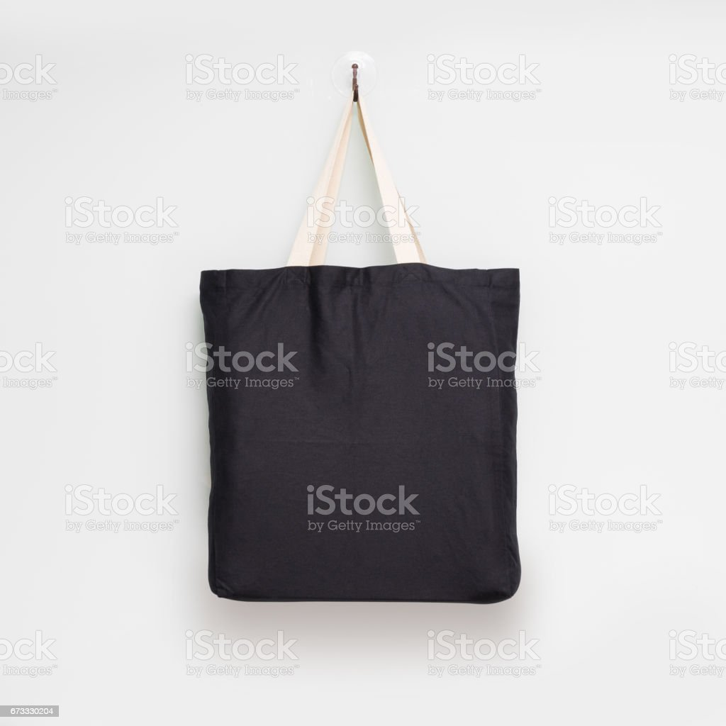 Hanging fabric bag on white wall background. Shopping pouch textile. - foto de stock