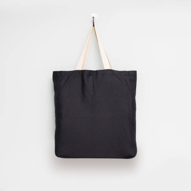 Hanging fabric bag on white wall background. Shopping pouch textile. stock photo