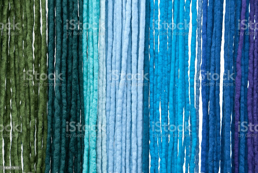Hanging felt ribbons shades from green to blue background royalty-free stock photo
