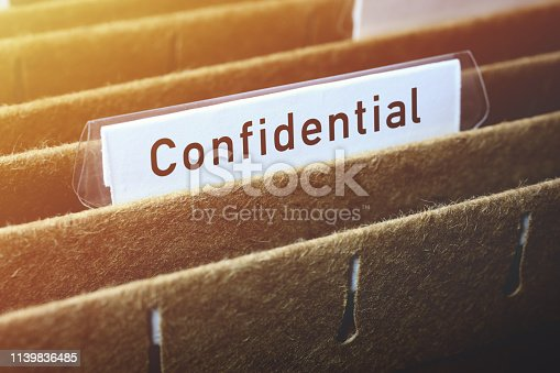 Close-up on hanging file labelled confidential in filing cabinet.