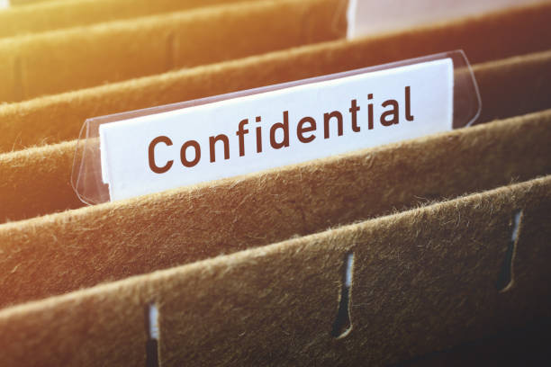 Hanging File Labelled Confidential Close-up on hanging file labelled confidential in filing cabinet. confidential stock pictures, royalty-free photos & images