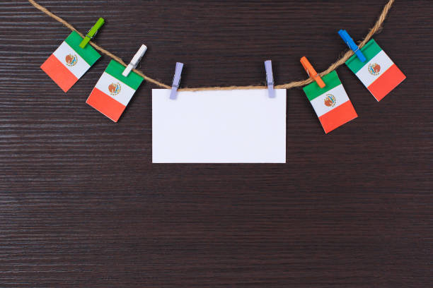 Hanging flags of Mexico attached to rope with clothes pins with copy space on white note paper stock photo