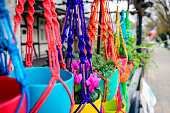 Flowers hanging in colorful pots on the street