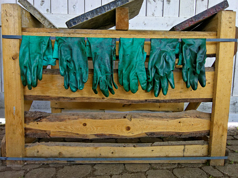 dirty gloves hanging on awooden rack