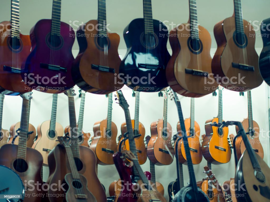 hanging guitars for sale in music store stock photo