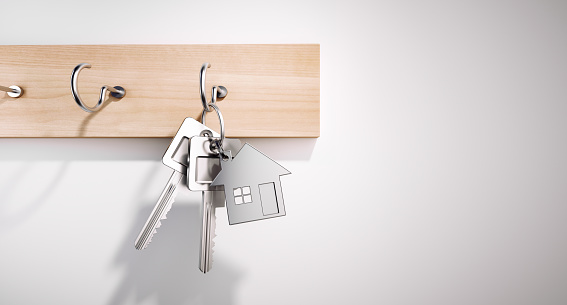 House Keys with Key Ring hanging on wooden Board