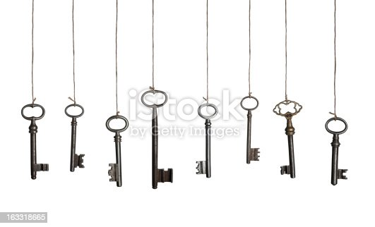 Old keys on strings, hanging in a row. Isolated on white.