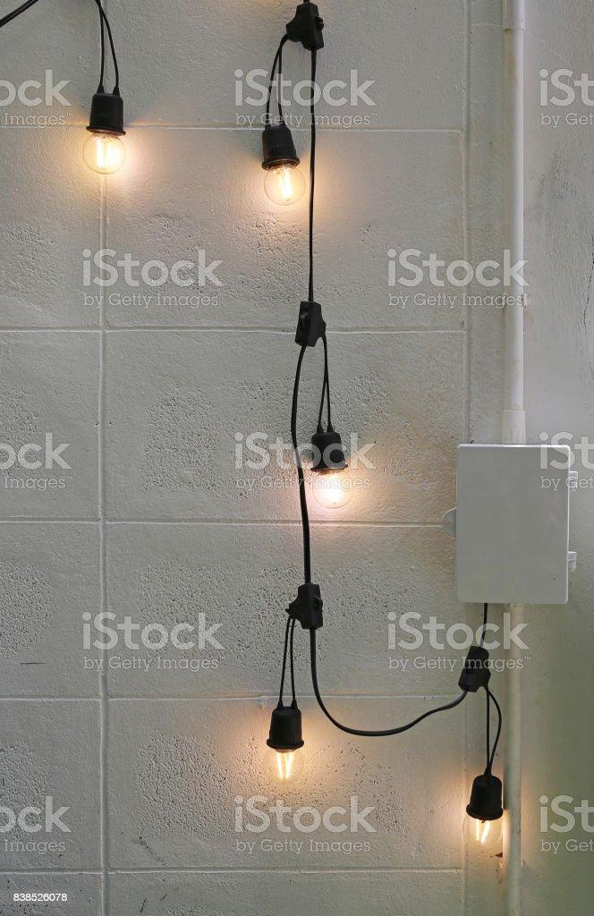 Hanging Light Bulbs at brick wall. stock photo