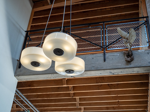 Hanging light fixture with fixed owl near second story of an open beam building