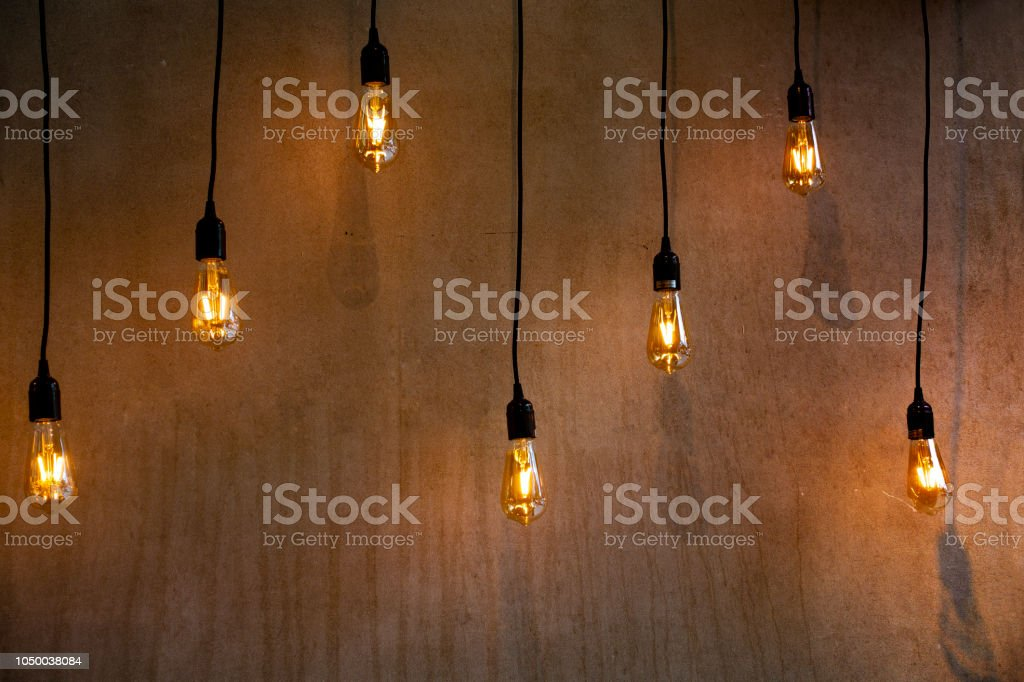Lighted lights in a dark room near a wall body with stylized bulbs