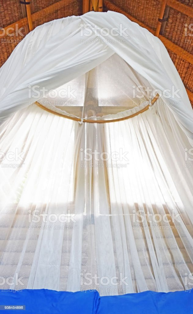 hanging mosquito net above the bed in tropical regions stock photo