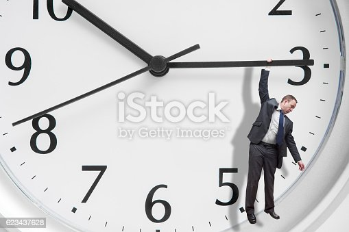 A symbolic studio shot of a middle aged businessman hanging on the end of the minute hand of an oversized clock.