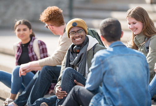 A multi ethnic group of university students are hanging out outdoors on campus.