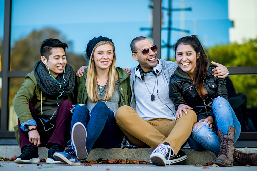 A multi-ethnic group of young adults are outdoors in an urban setting. They are sitting outside a store and embracing. They are wearing trendy clothing.