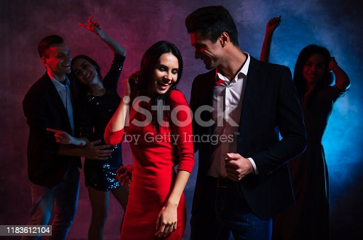 497317250 istock photo Hanging out with friends. Two young and attractive couples and one gorgeous woman are dancing together in the smoke and lights of the club, celebrating New Year's Eve or Christmas. 1183612104
