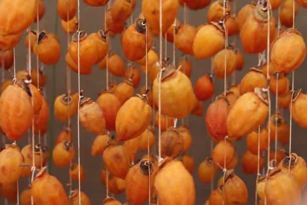 Hängende Persimmon - Japanische getrocknete Persimmon (Hoshigaki) an Schnüren aufgehängt, um einen gemeinsamen Anblick zu trocknen – Foto