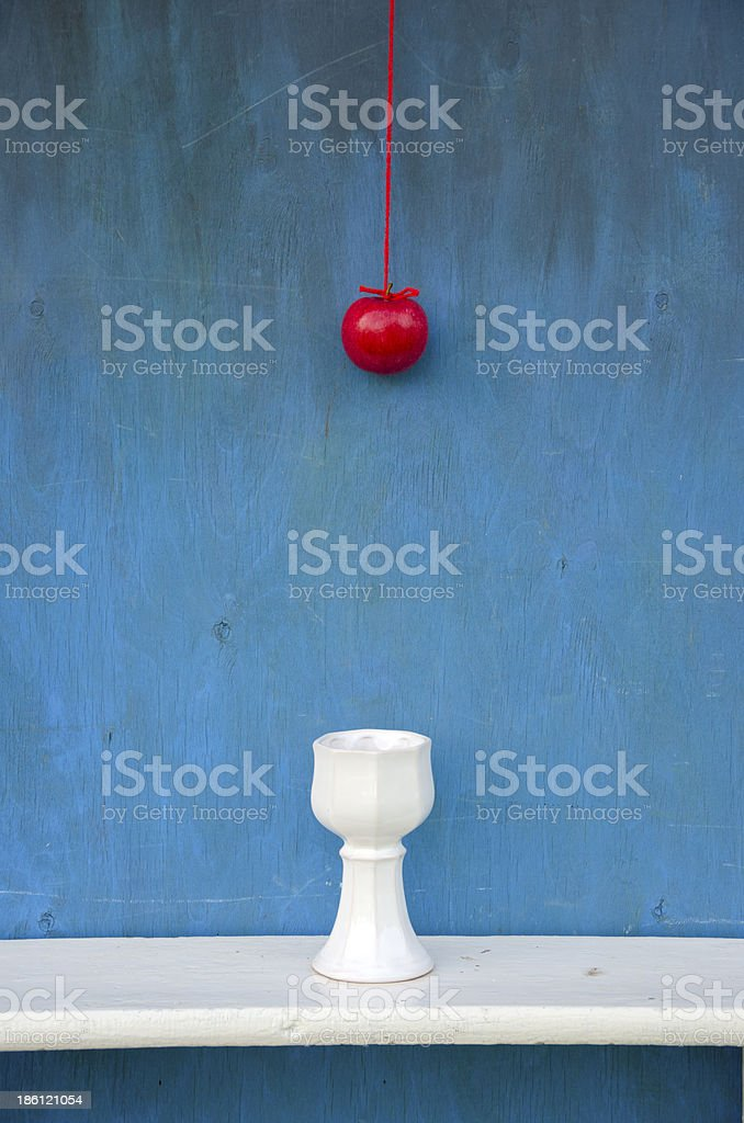 hanging red apple on string and white vase royalty-free stock photo