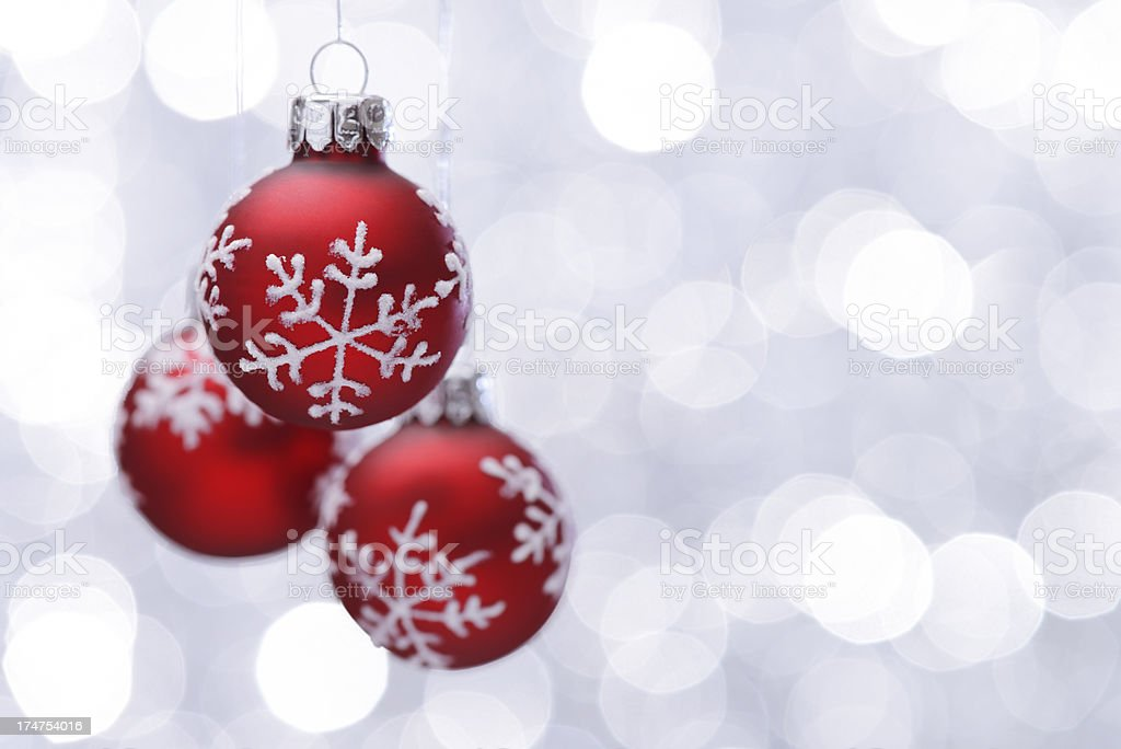 Hanging red christmas balls on silver illuminated background royalty-free stock photo
