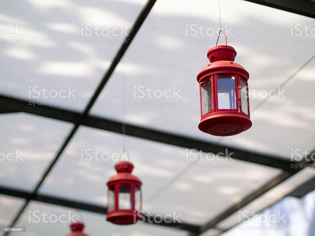 A row of red lantern hanging down from metal frame with transparent...