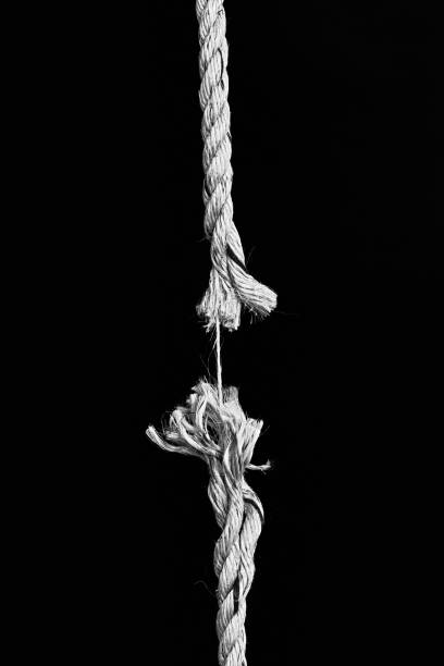 Hanging rope, frayed to its last strand, about to snap stock photo