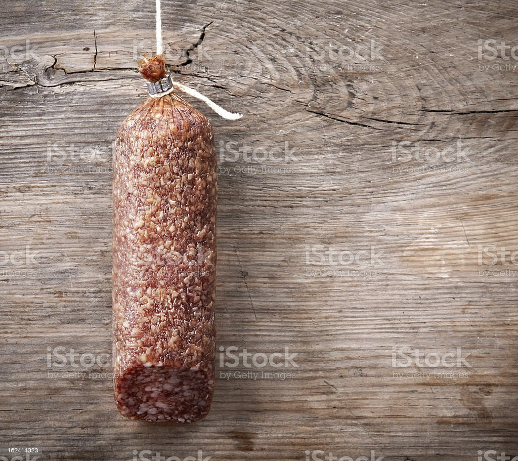 hanging salami sausage on wooden background royalty-free stock photo