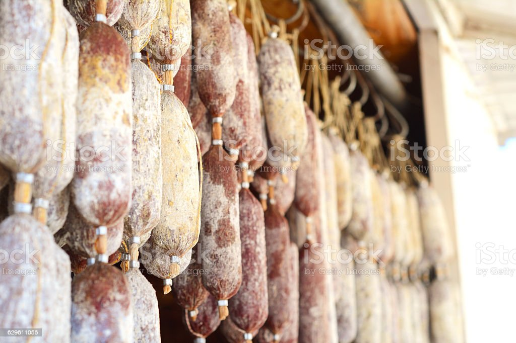 Hanging salami sausages in street market. stock photo