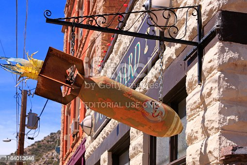Hanging sign in the shape of a WW2 aerial bomb outside the Courtyard Restaurant on Brewery Ave in Bisbee, AZ
