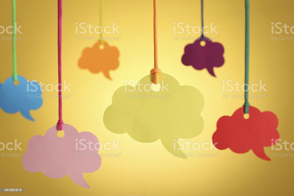 Hanging blank speech bubble on yellow background.