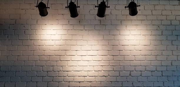 spot suspendu illuminent au fond blanc de mur de brique avec l'espace de copie - spot photos et images de collection