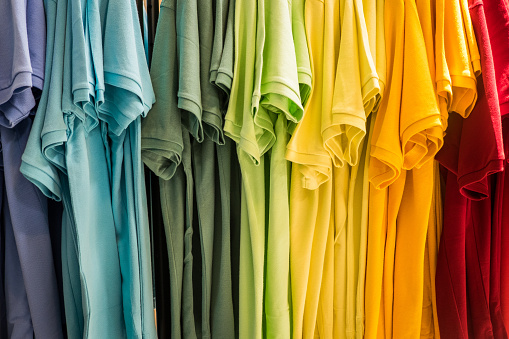 Hanging t shirts arranged in rainbow colors.