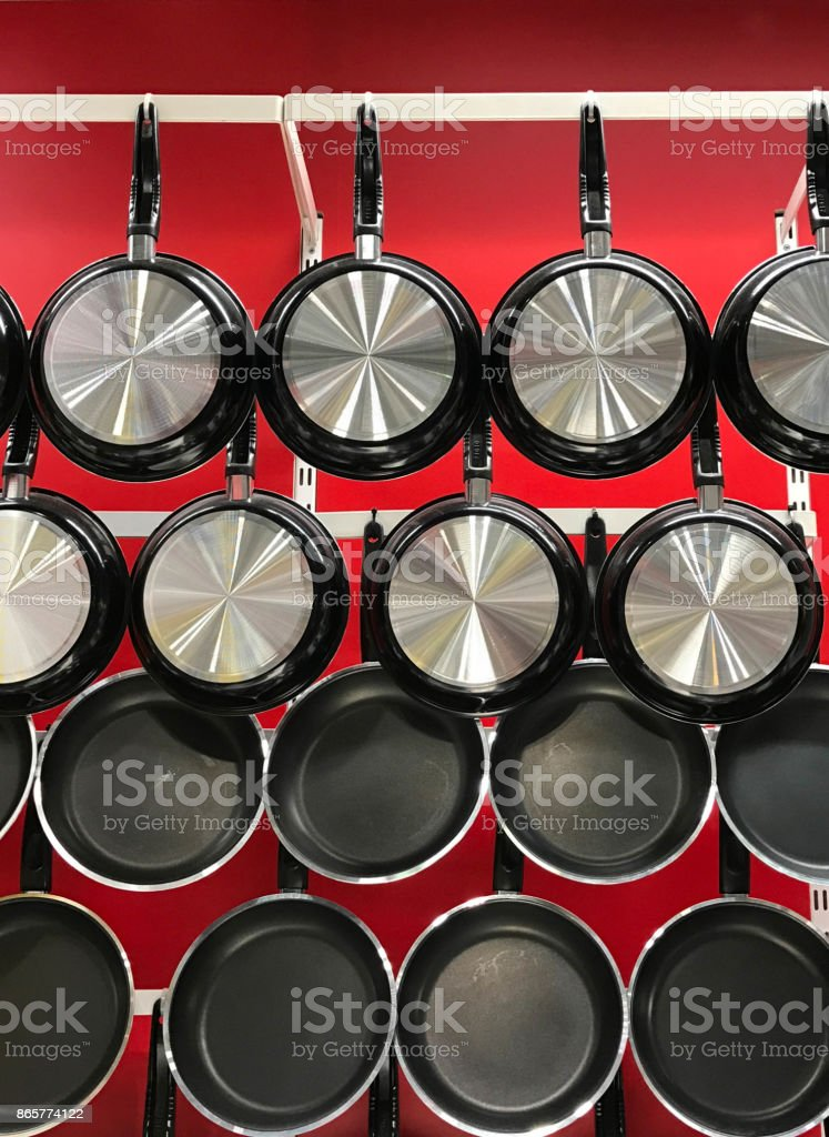 Hanging teflon pans on red wall stock photo