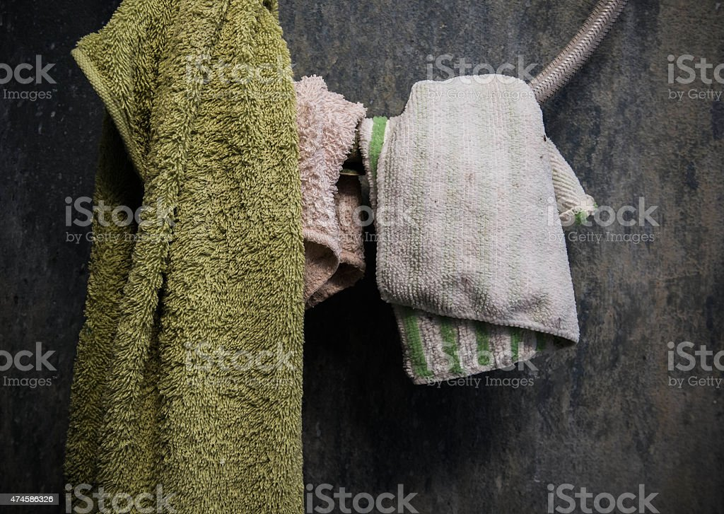 Hanging towel and cotton on shower wire Hanging towel and cotton on shower wire with old dirty wall 2015 Stock Photo