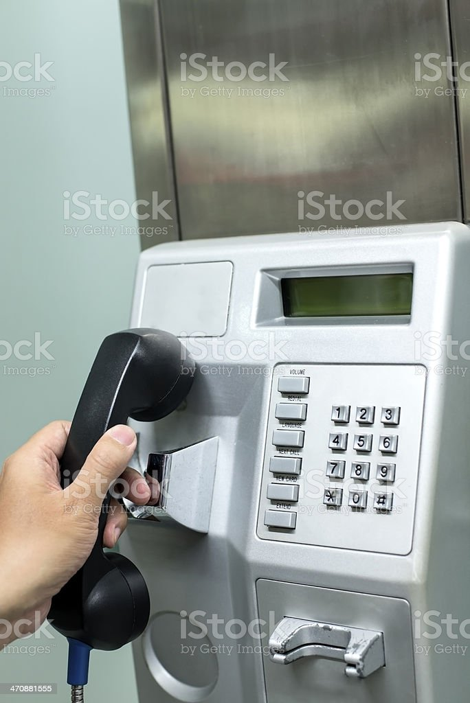 Close-up of hand hanging up pay phone receiver.