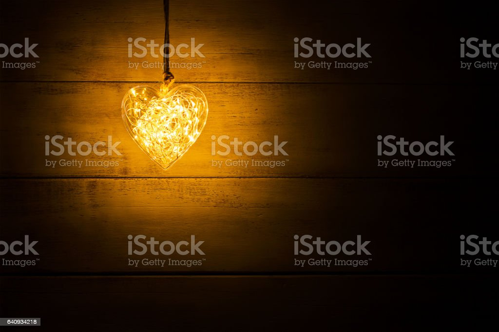 Hanging warm glowing orange heart stock photo