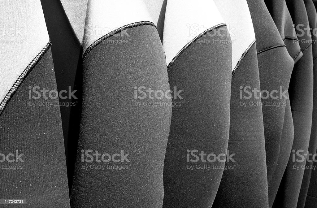 Hanging wetsuits stock photo