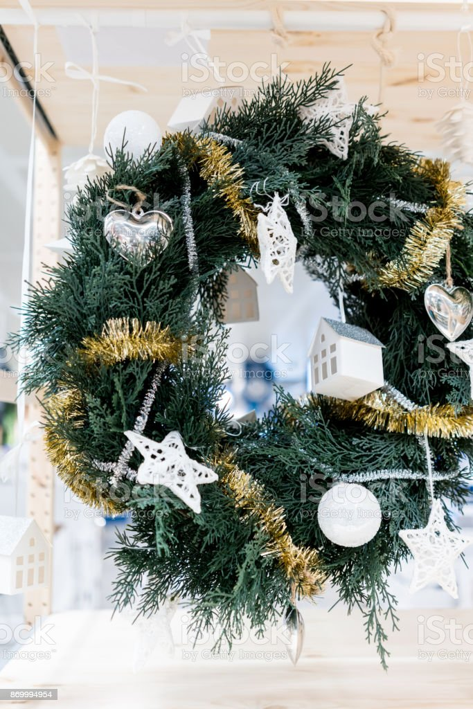 Hanging white and silver decorative Christmas wreath with tinsel garland, hanging heart and ornaments for seasonal greeting. stock photo