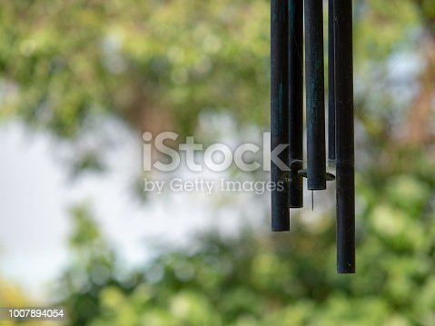 Some hanging wind chimes hanging in a backyard on a sunny day