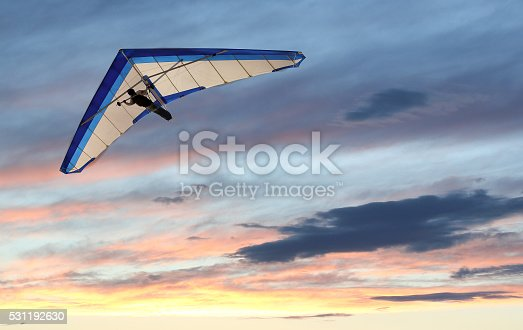 Hanglider Flying over the ocean at sunset